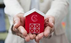家の模型を両手で支え家づくりへの想いを表すイメージ写真